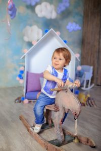 little boy playing on wooden horse